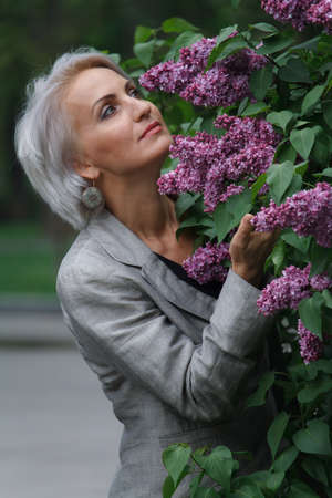 Mature blonde woman in gray suit walks in public garden, admires flowers and smiles, selective focus