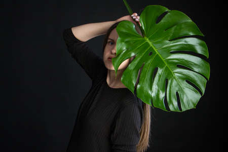 Portrait of beautiful woman with green tropical leaf on black background