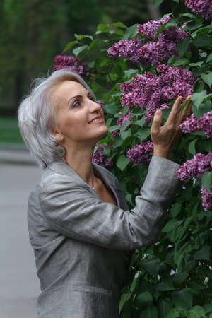 Mature blonde woman in gray suit walks in garden, admires flowers and smiles, selective focus