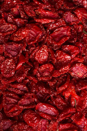 Close-up sun-dried tomatoes with spices and olive oil, background or concept, selective focus