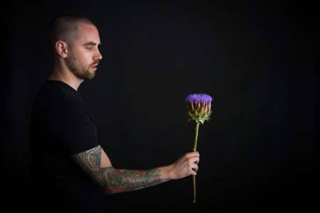 Portrait of young man holding purple artichoke flower on black background, greeting card or concept Stok Fotoğraf
