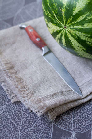 Fresh ripe watermelon on linen tablecloth next to knife, preparing for picnic, selective focus