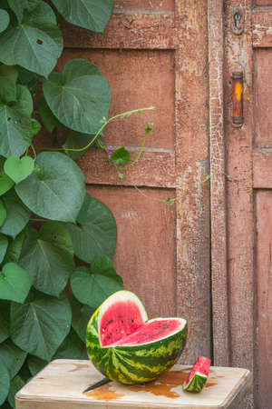 Fresh red ripe watermelon on wooden cutting board near old door to village house, picnic concept, selective focus