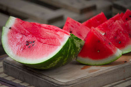 Fresh red ripe watermelon on wooden cutting board, picnic concept, selective focus
