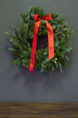 Stylish minimalistic christmas fir branches wreath with red bow on gray background, copy space, greeting card