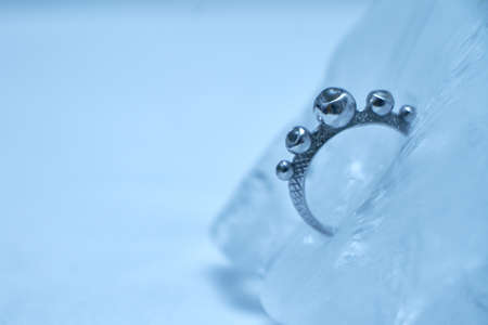 Close up silver ring frozen into ice on white background, selective focus