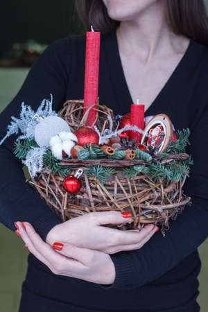 Female hands holding new year composition of fir branches, christmas decorations and candles, gift concept, selective focus Archivio Fotografico