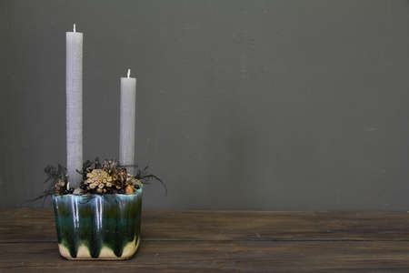 Minimalistic christmas composition with pine branches, cones and candles on wooden table