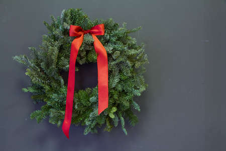 Stylish minimalistic christmas fir branches wreath with red bow on grey background, copy space, greeting card