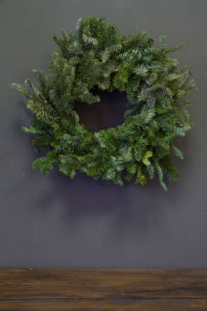 Stylish minimalistic christmas fir branches wreath on grey background, copy space, greeting card