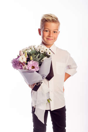 Cheerful blond fashionable boy gives bouquet on white studio background, gift delivery flowers, Spring Womens Day Archivio Fotografico