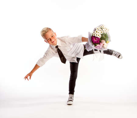 Cheerful blond fashionable boy gives bouquet in flighton white studio background, gift delivery flowers, Spring Womens Day
