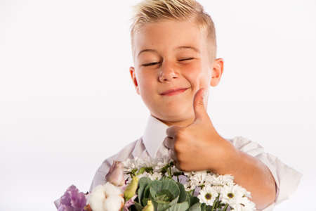 Cheerful blond fashionable boy gives bouquet and thumbs up on white studio background, gift delivery flowers, Spring Womens Day Archivio Fotografico