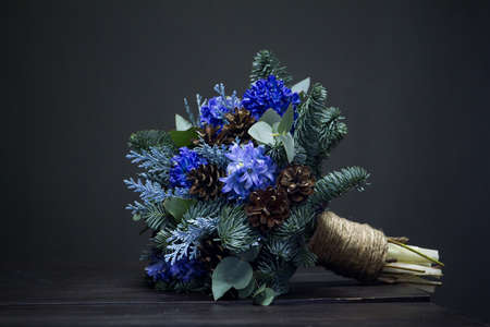 Winter bouquet of Nobilis fir twigs, blue hyacinths and cones, winter gift concept Archivio Fotografico