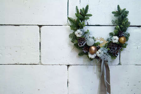 Christmas horseshoe wreath of vines decorated with fir branches, Christmas balls and natural materials, New Year concept