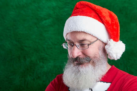 Mature bearded man with eyeglasses on his face wearing Santa hat, green artificial Christmas tree background, copy space Archivio Fotografico