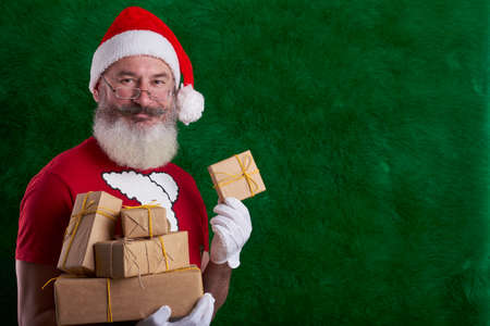 Mature bearded man wearing Santa hat with many gifts in hand, green artificial Christmas tree background, copy space