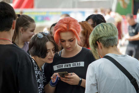 Kharkiv, Ukraine - July 26, 2020: Company of modern informal youth at the festival, couple of girls use phone, youth mob in big city