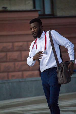 Kharkiv, Ukraine - July 26, 2020: Young doctor of African nationality walking outdoors with stethoscope on his neck
