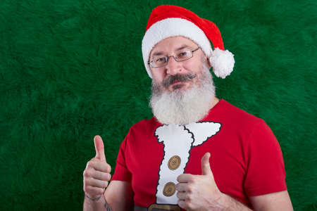 Mature bearded man with eyeglasses on his face wearing Santa costume and thumbs up, Santa smiling and looking at camera, copy space Archivio Fotografico
