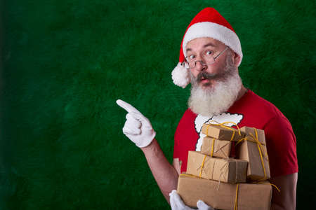 Mature bearded man wearing Santa hat with many gifts in hand, Santa points with forefinger to something, copy space Archivio Fotografico