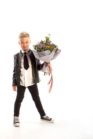 Cheerful blond fashionable boy gives bouquet on white studio background, gift delivery flowers, Spring Womens Day Reklamní fotografie