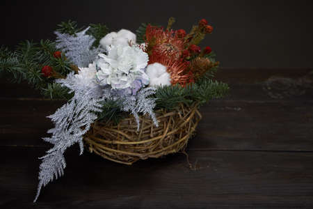 Christmas or New Year composition. Wicker basket with fir branches decorated by natural materials on gray background Reklamní fotografie