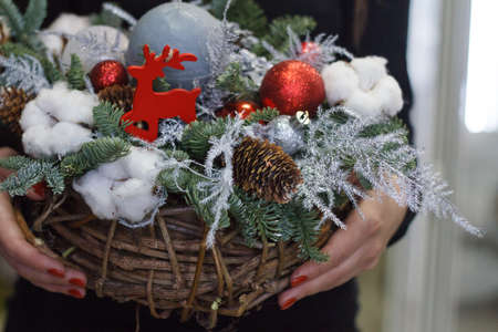 Female hands holding christmas composition of fir branches, new year decorations and candles, gift concept, selective focus Archivio Fotografico