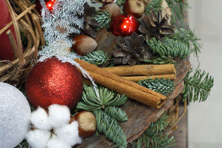 Christmas or New Year composition. Wicker basket with fir branches decorated by natural materials on gray background Archivio Fotografico