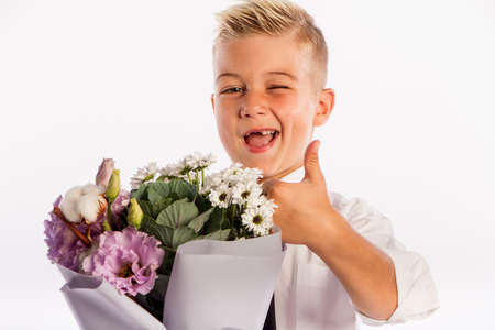 Cheerful blond fashionable boy gives bouquet and thumbs up on white studio background, gift delivery flowers, Spring Womens Day Reklamní fotografie