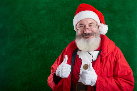 Mature bearded man with eyeglasses on his face wearing Santa hat, Santa shows two thumbs up, copy space Reklamní fotografie