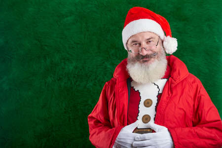 Mature bearded man with eyeglasses on his face wearing Santa hat, Santa smiling and looking at camera, copy space