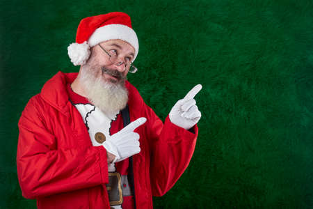 Mature bearded man with eyeglasses on his face wearing Santa hat, Santa points with both hands to something, copy space Reklamní fotografie