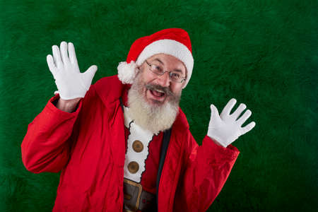 Mature bearded man with eyeglasses on his face wearing Santa hat, funny santa smiling and waving his hands, copy space