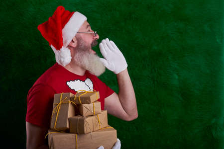 Mature bearded man wearing Santa hat with lot of gifts in hand, Santa put hand to face and shouts, copy space Reklamní fotografie
