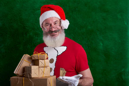 Mature bearded man wearing Santa hat with lot of gifts in hand, Santa smiling and looking at camera, copy space