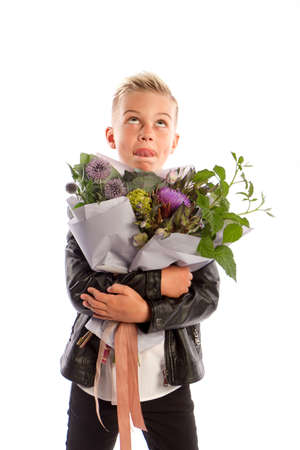 Cheerful blond fashionable boy gives bouquet on white studio background, delivery flowers, Spring Womens Day