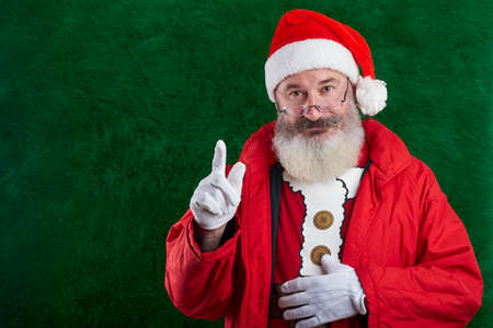 Mature bearded man with eyeglasses on face wearing Santa hat, raised forefinger, attention sign, copy space Reklamní fotografie