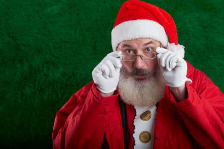 Mature bearded man with eyeglasses on face wearing Santa hat, Santa surprised and looks at camera, copy space