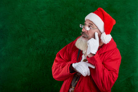 Mature bearded man with eyeglasses on face wearing Santa hat, Santa looks away at something, copy space Reklamní fotografie