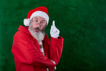 Mature bearded man with eyeglasses on his face wearing Santa hat, Santa has an idea sign, copy space
