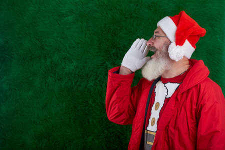 Mature bearded man with eyeglasses on face wearing Santa hat, Santa put hand to face and shouts, copy space