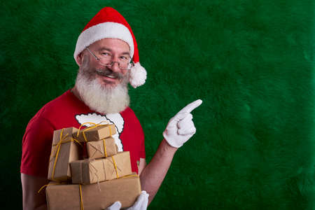 Mature bearded man wearing Santa hat with lot of gifts in hand, Santa points with forefinger to something, copy space Reklamní fotografie