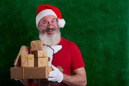 Mature bearded man wearing Santa hat with many gifts in hand, Santa smiling and looking at camera, copy space