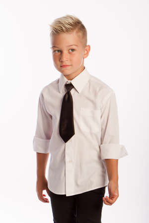 Studio portrait of stylish caucasian blond boy in shirt and tie, white background, copy space Reklamní fotografie