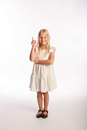 Studio portrait of fashionable little girl with index finger up. Isolated white background.