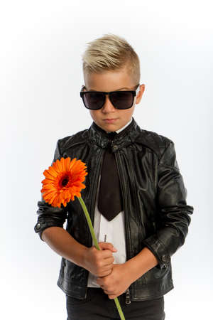 Studio portrait of fashionable blond caucasian boy with single gerbera flower, white background, copy space