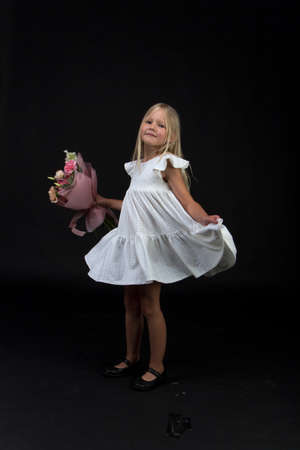 Studio portrait of cute blonde girl in white dress with beautiful gift bouquet, black background, selective focus