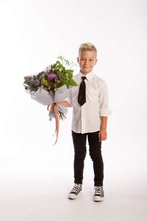 Studio portrait of fashionable blond caucasian boy with gift bouquet, white background, copy space