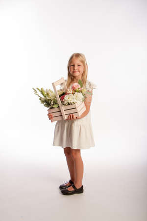 Studio portrait of cute blonde girl in white dress with wooden basket of flowers, white background, selective focus Reklamní fotografie